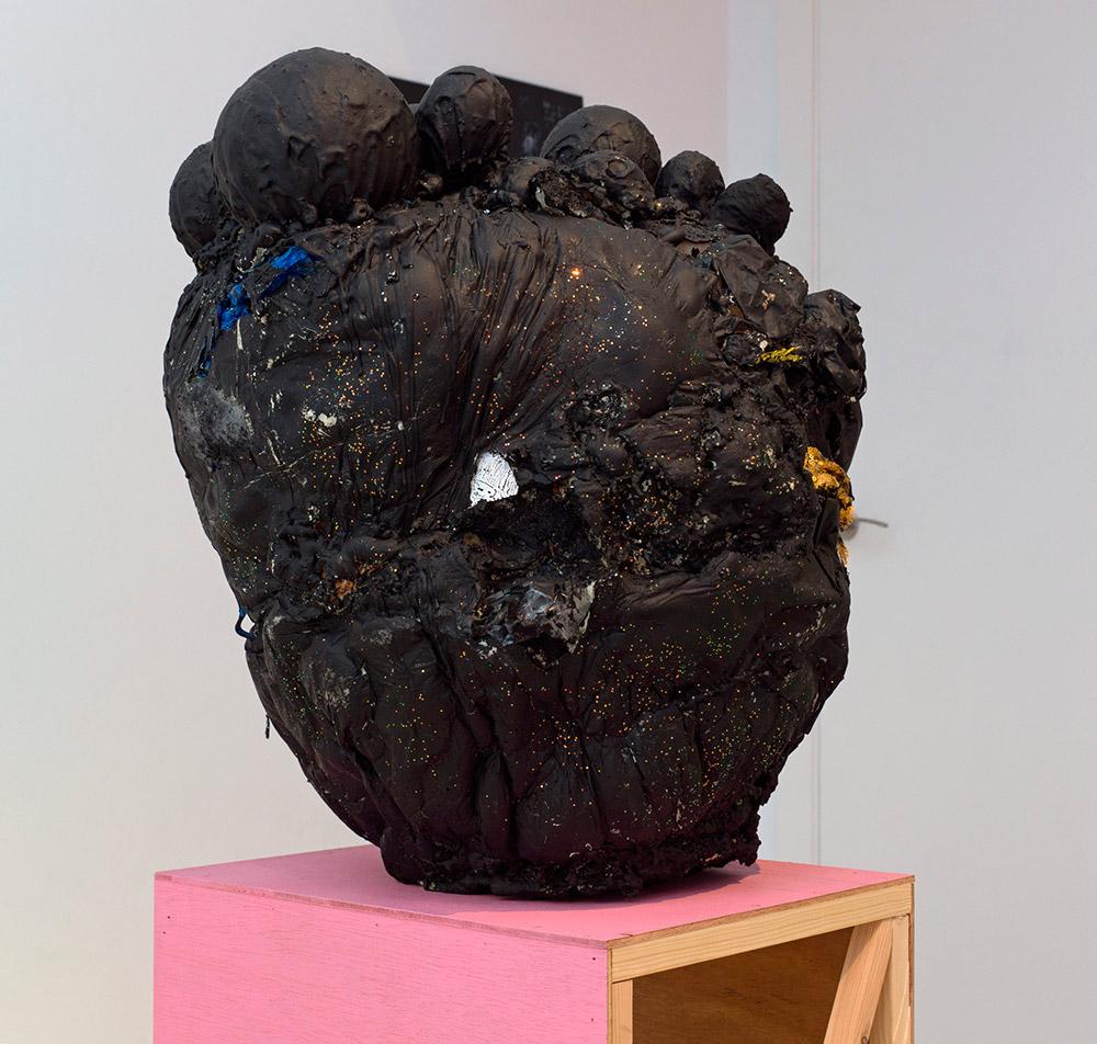 """""""Golden trolley loveboy"""", jesmonite, espuma de poliuretano, pintura acrílica, telas, residuos plásticos y purpurina, 65 x 45 x 65 cm. Pedestal de madera y esmalte en spray, 35 x 40 x 60 cm. Javier Chozas, 2017"""