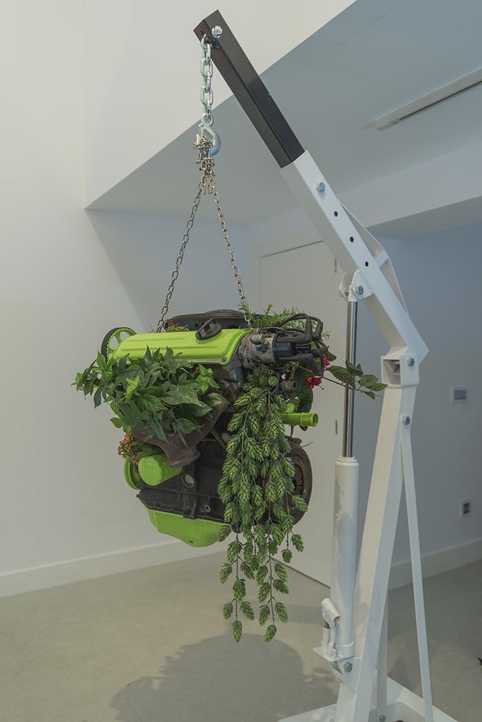 """""""Planet Earth, Volks Wagen"""", motor de desguace, pintura monocapa acrílica verde, grasa y plantas de poliéster, suspendido con una grúa de taller, medidas variables. Manuel Franquelo Giner, 2017"""